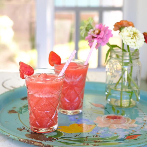Two glasses of pretty pink cocktails garnished with a strawberry.