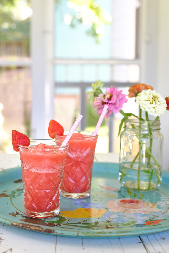 Two glasses of Strawberry Frosé on a blue vintage tray with a mason jar filled with zinnias
