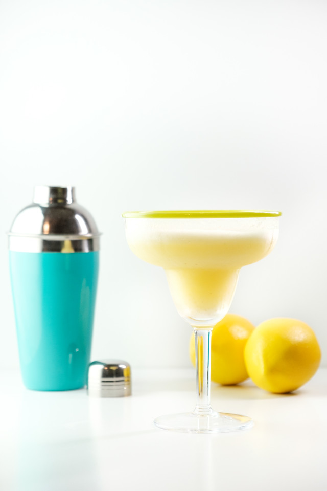Blue cocktail shaker with margarita and lemons on a white background