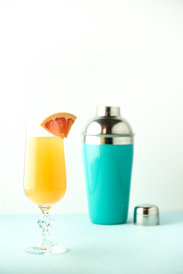 Blue cocktail shaker and and orange cocktail garnished with a grapefruit slice