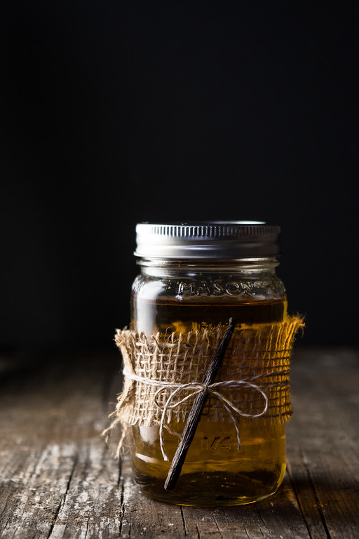 Mason jar filled with brown liquid, tied with burlap and a vanilla bean