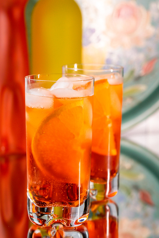 Two glasses filled with a bright orange cocktail garnished with an orange wedge.