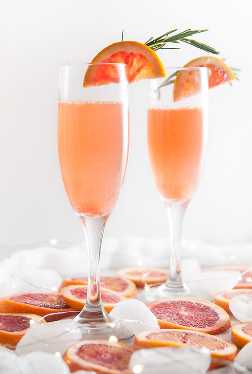 Blood Orange Mimosa in two glasses garnished with blood orange slices