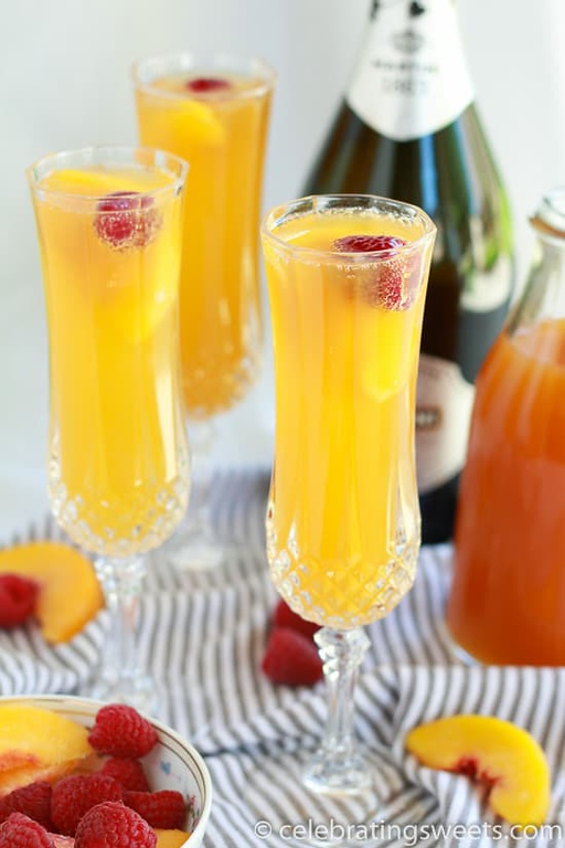Raspberry Peach Mimosas in several glasses.