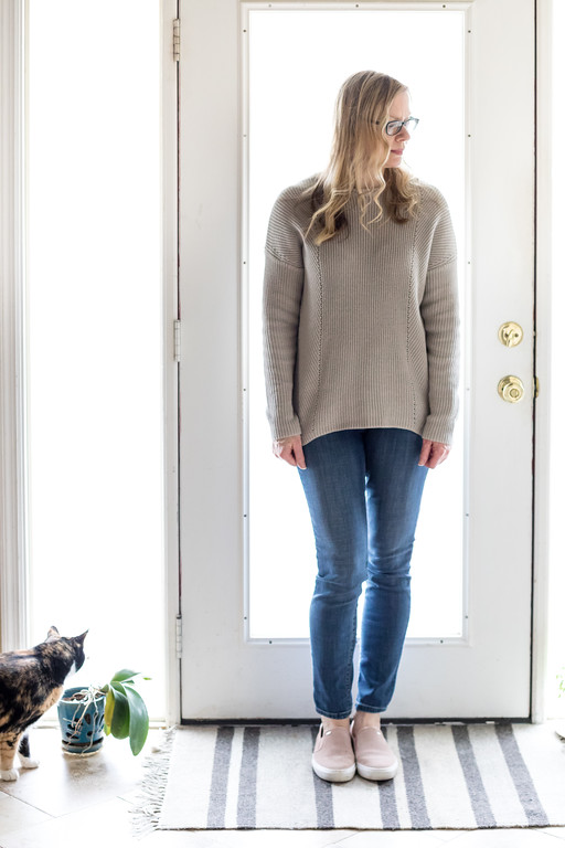 Woman dressed in beige sweater, jeans and blush flats with a kitty cat.