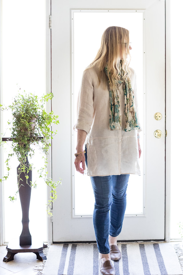 woman walking with ivory tunic, scarf and jeans in front of a door.