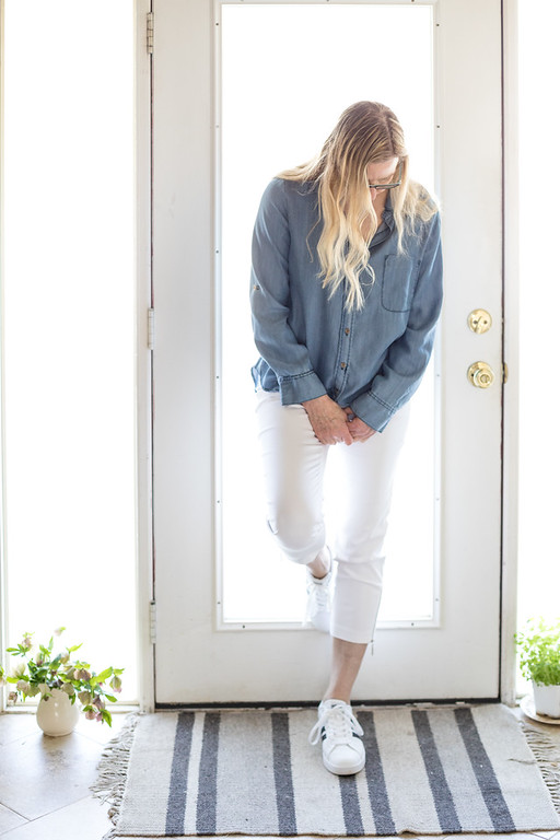 Woman in white pants, adidas, and chambray shirt.