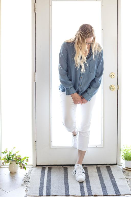 Woman in white pants, adidas, and chambray shirt.