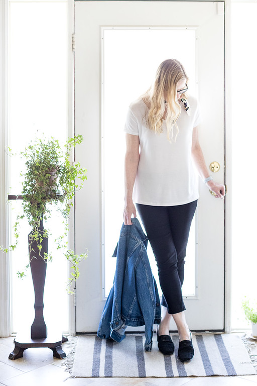 Woman in white t shirt, black pants, black shoes and jean jacket