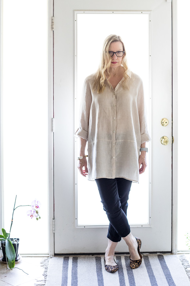 Woman in door with ivory linen tunic, black pants, and leopard flats