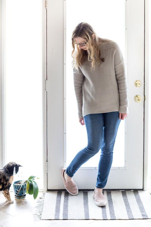 Fashion - woman in beige sweater, jeans, blush shoes and kitty cat in front of a door.