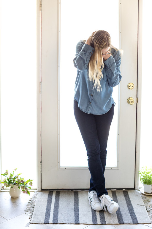 Woman wearing dark jeans, chambray top, Adidas sneakers