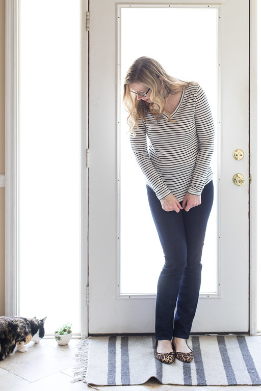 Woman with stripped top, dark jeans, leopard flats and a kitty cat.
