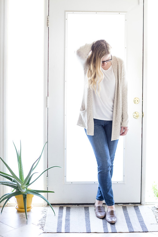 Woman in Neutral Cardigan in jeans and flats in front of door