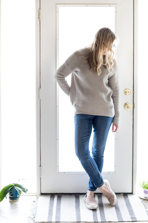 Woman in neutral beige sweater, jeans and pink loafers.