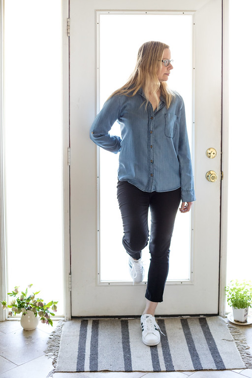 Fashion over 50 - woman in black skinny pants, chambray top and adidas shoes.