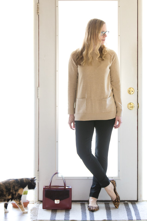 Fashion over 50 woman in camel sweater with black leggings and Kate Spade purse with kitty cat photobombing