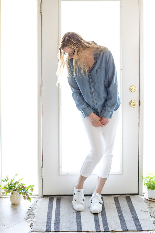 A woman in a chambray shirt, white pants and adidas shoes in front of a door.