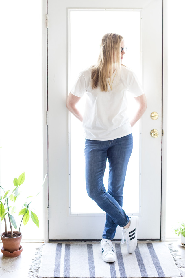 Woman in a white t shirt, denim jeans and addidas.