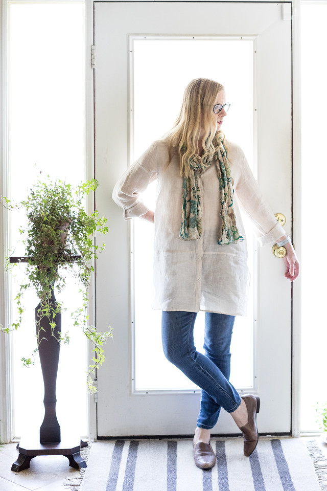 Linen tunic, blue jeans and taupe shoes on woman in front of a door.