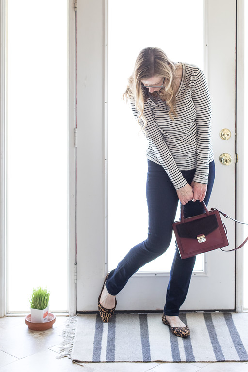 woman in front of door with dark jeans, stripped shirt, kate spade purse, and adrienne Vittadini scarf.
