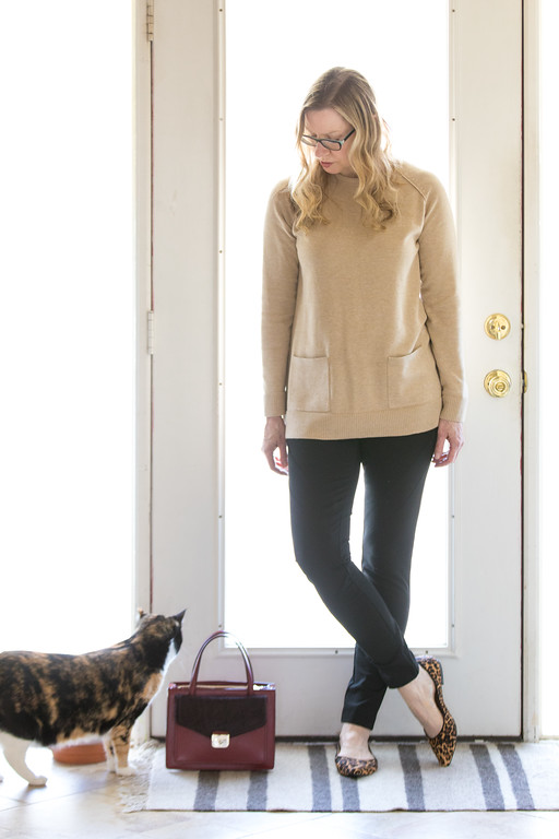 Woman in camel sweater, black leggings, leopard flats, Kate Spade purse, and kitty cat for a winter capsule wardrobe