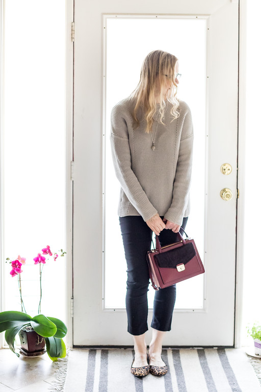 Woman with neutral sweater, black skinny pants, leopard flats and kate spade purse.