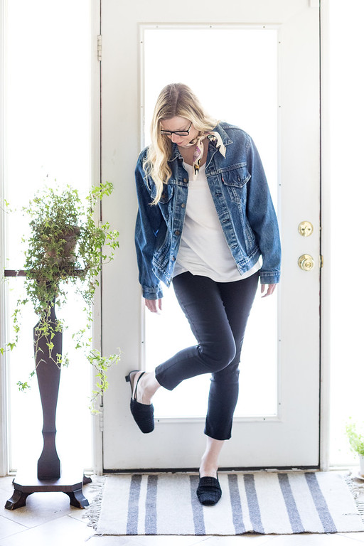 Woman in jean jacket, white t shirt, black pants and black shoes