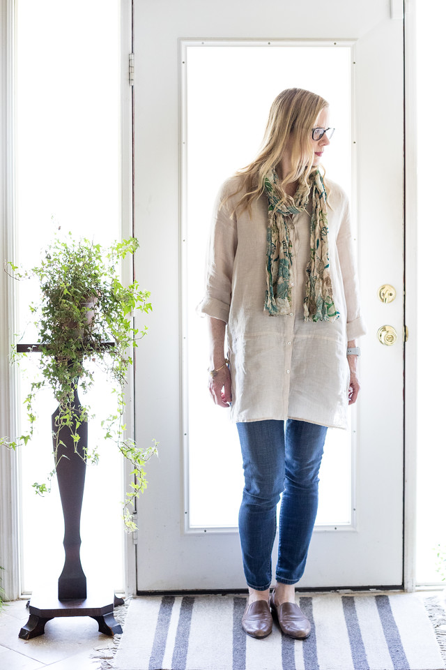 Woman in front of door wearing a linen tunic, a scarf, jeans, flat loafers with plant stand