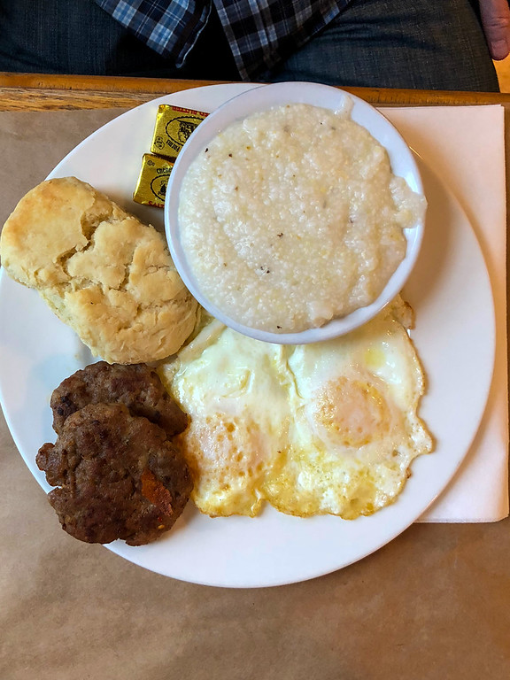 Overhead shot of eggs, sausage, biscuits, and grits from Early Girl Eatery.