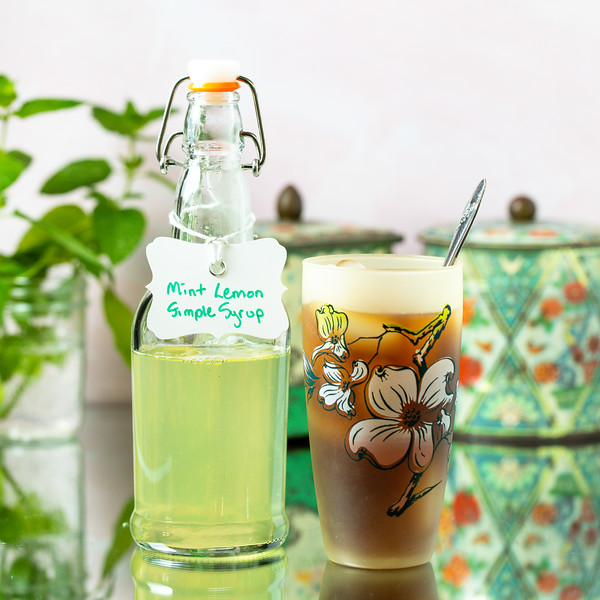 "Bottle labeled ""mint simple syrup"" next to a glass of tea."