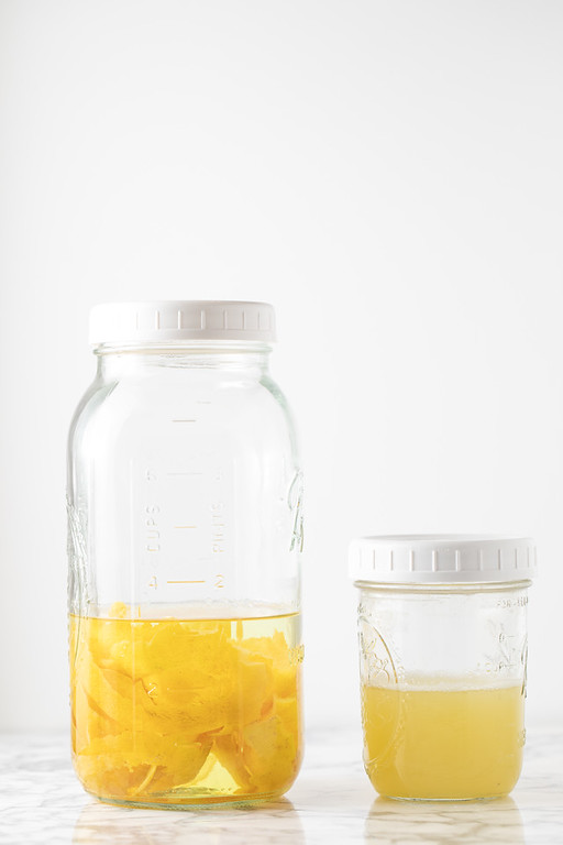 Jar filled with vodka and lemon peels and a second jar with lemon juice.
