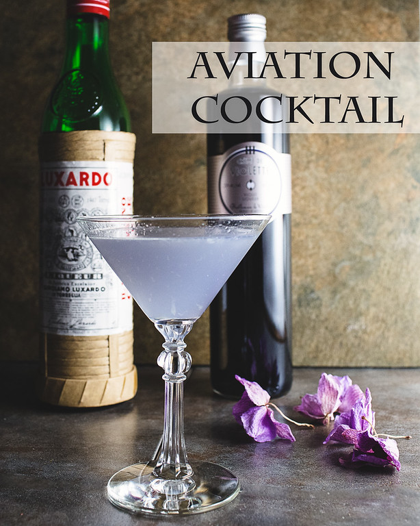 Lavender colored cocktail in front of two bottles on a stone background with text overlay reading Aviation cocktail
