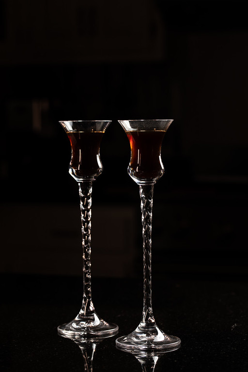 Two tall glasses with coffee liqueur in them.