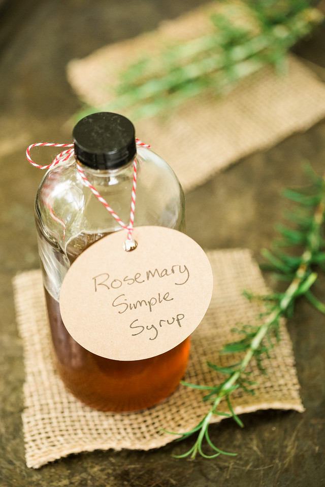 Bottle filled with a brown liquid on a burlap with rosemary sprigs. Tag on bottle reads Rosemary Simple Syrup