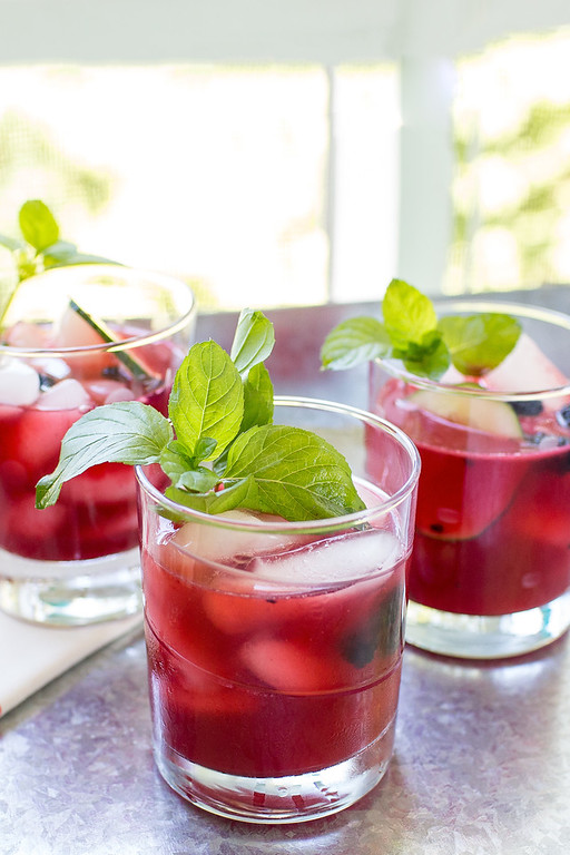 3 glasses of a bright red blackberry cocktail garnished with mint.