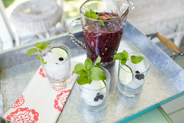 Pitcher of blackberry cocktails with glasses filled with ice and garnished with blackberries and mint.