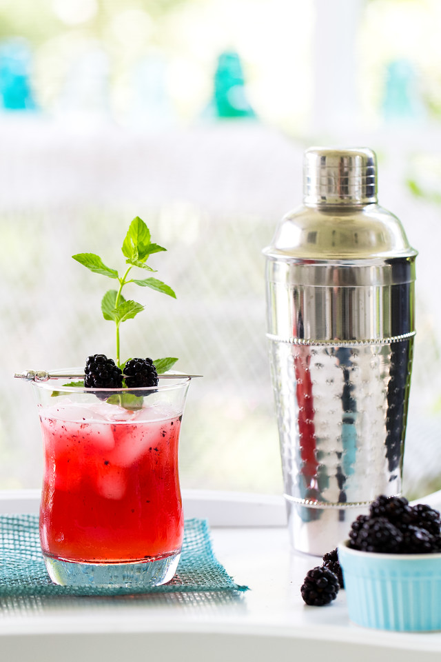 Bright red cocktail with blackberries and mint and a cocktail shaker
