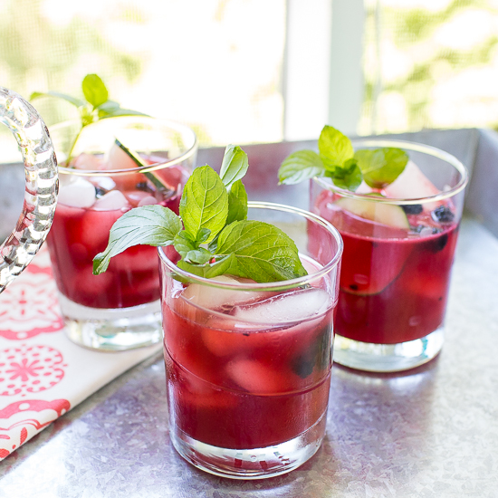 Three glasses filled with blackberry cocktail garnished with mint.