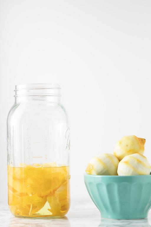 Lemon zest in jar with vodka with zested lemons on the side.