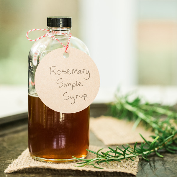 Bottle filled with a brown liquid with a rosemary sprig nearby and a tag reading Rosemary Simple Syrup