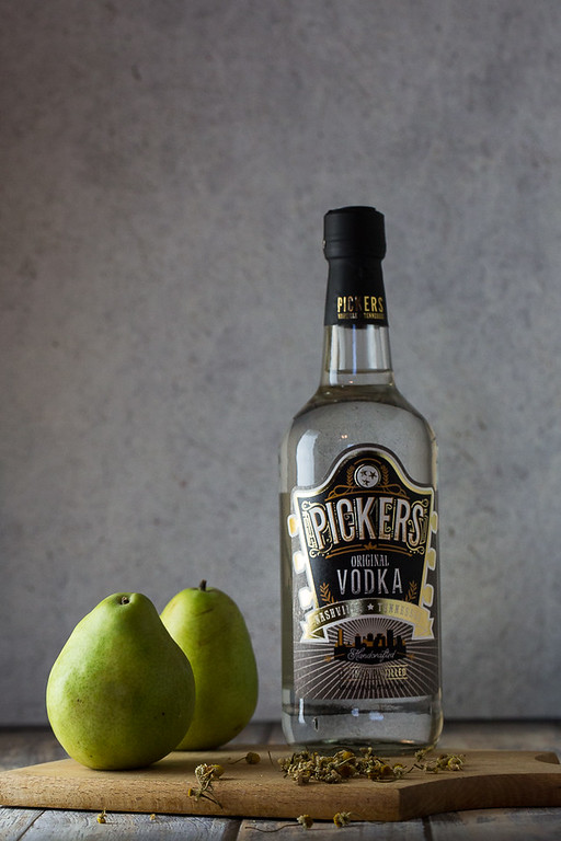 Two pears, chamomile flowers and a bottle of Pickers vodka.