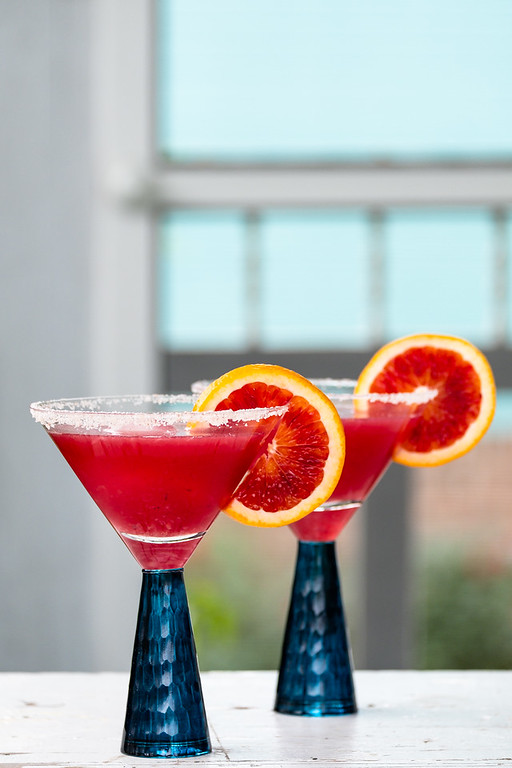 Two bright red blood orange margarita cocktails garnished with blood orange slices.