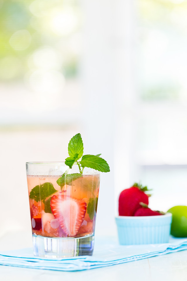 A glass filled with a strawberry mojito garnished with mint with strawberries in the background