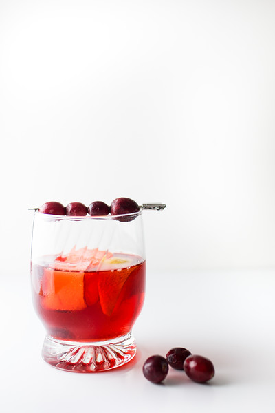 Red cocktail garnished with cranberries.
