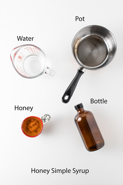 Ingredients to make honey simple syrup - water, honey, pot, and bottle.
