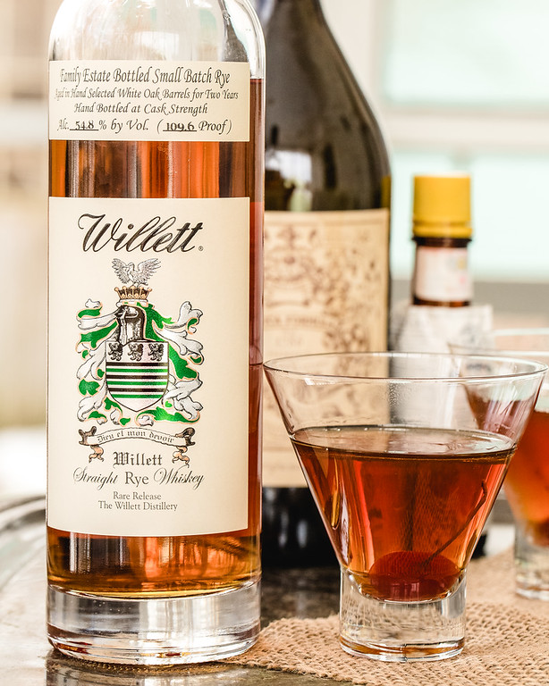 Bottle of Willett Rye Whiskey with a Manhattan Cocktail next to it.