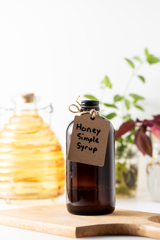 A brown bottle with the tag reading Honey Simple Syrup.