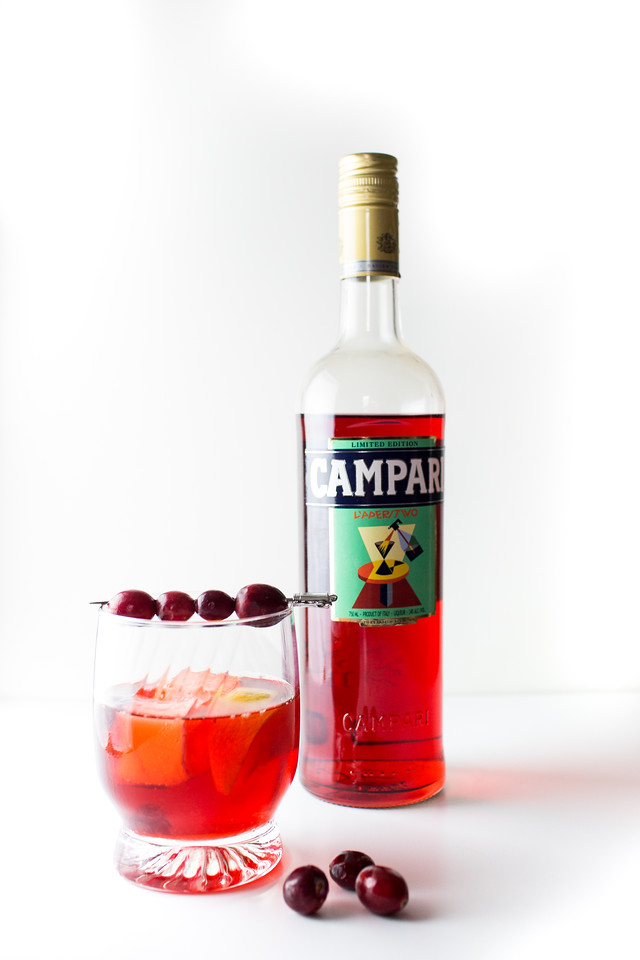Red cocktail garnished with cranberries and a bottle of Campari behind it.