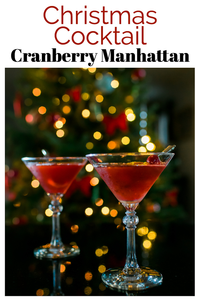 Two martini glasses filled with a red cocktail in front of a Christmas tree. Text reads Christmas Cocktail Cranberry Manhattan.